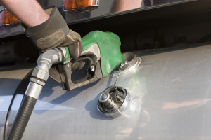 Trucker pumping gas and filing with Express IFTA for his IFTA tax report
